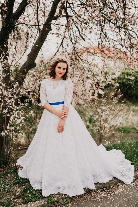 čipkované svadobné šaty s modrým pásom